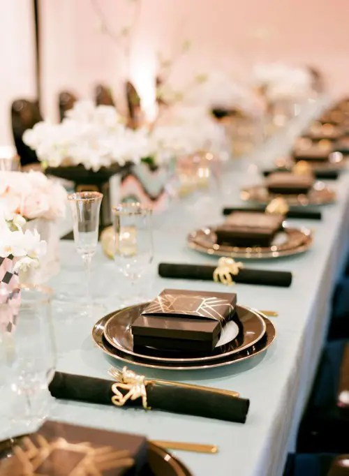 black and gold wedding decor, blush bloom centerpieces and a blue tablecloth