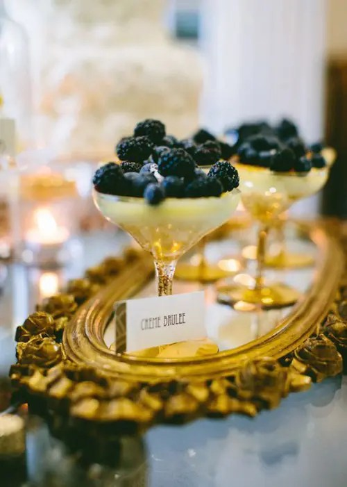 a wedding dessert setting with a refined gold tray, black and gold berry desserts