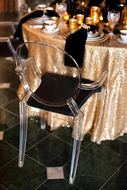 gold sequin tablecloths, black napkins and acrylic and black chairs