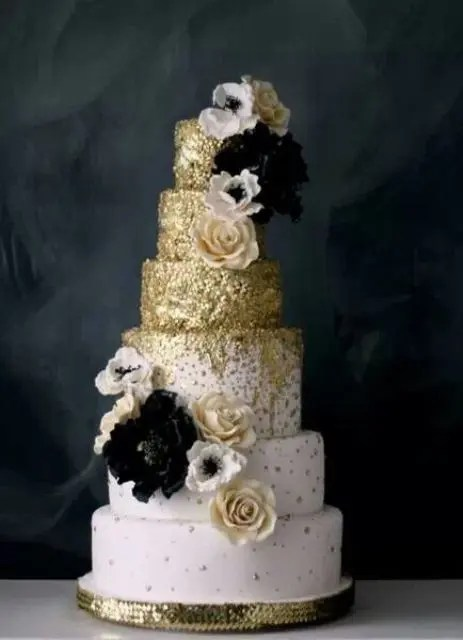 a white wedding cake decorated with gold touches with black and white blooms