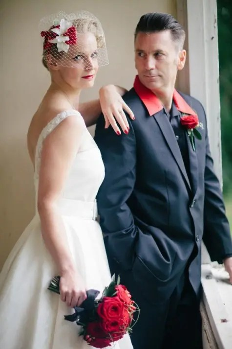 a groom wearing a black suit and a red shirt with a red rose boutonniere and a bride rocking red touches, too