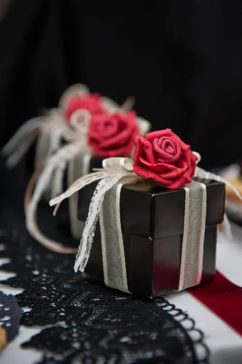 black boxes with white ribbons and red roses on top to pack wedding guest favors
