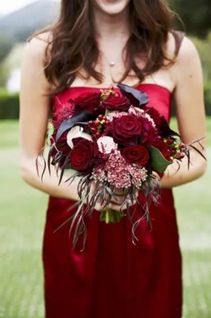 a bridesmaid bouquet with black callas and red blooms plus soem textural leaves