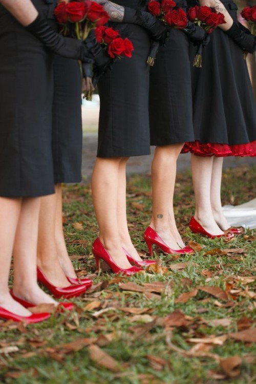 bridesmaids wearing black gowns, red shoes and carrying red rose bouquets