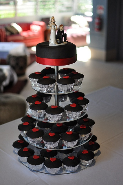 black cupcakes with red hearts on top plus a black wedding cake with red ribbons and cake toppers