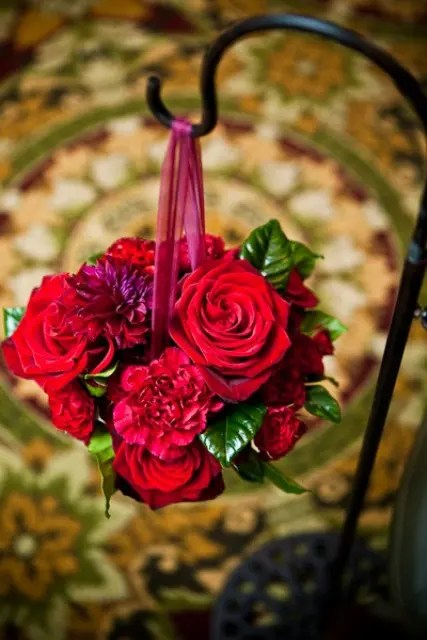 hot red bloom balls hanging on black metal holders for decorating the wedding aisle