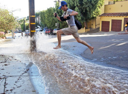 A man leaps over water flooding a side street after a water main break sent churning, muddy water down Sunset Boulevard and hilly side streets on the famed Sunset Strip in West Hollywood, Calif., Friday, Sept. 26, 2014. (AP Photo/Nick Ut)