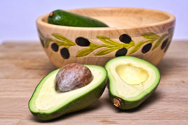 green sliced avocado on brown wooden table top