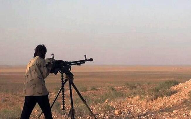 Militante do Estado Islâmico aponta arma durante batalha contra as forças do governo sírio em uma estrada entre Homs e Palmyra (maio/2015). Foto: AP