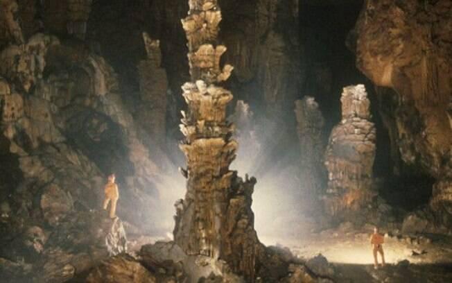Andrew Eavis e um colega observam uma grande formação rochosa no meio de uma caverna
