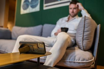 Photo of man sitting on sofa with CLCKR holding phone in landscape mode on coffee table