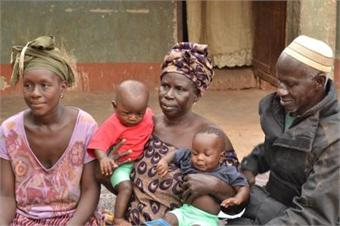 Majai sits with the traditional birth attendant and Sheriff who helped to save hers and her babies life