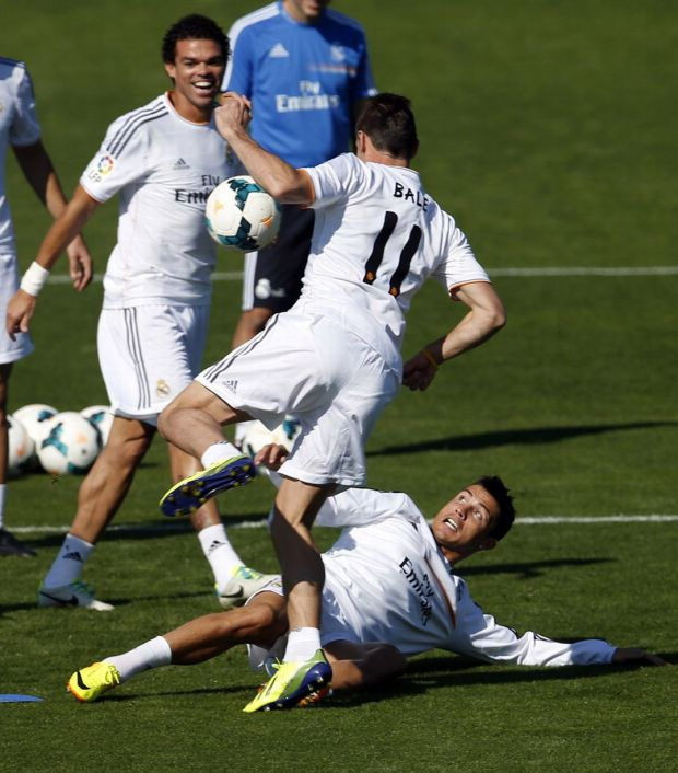 Gareth Bale is tackled by Cristiano Ronaldo as Pepe looks on