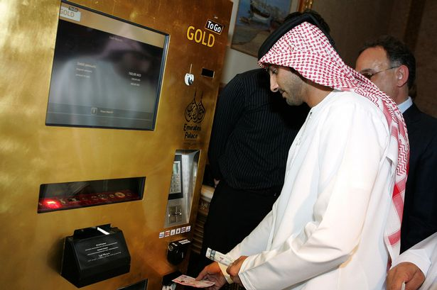 """An Emirati man tries the """"Gold to Go"""" vending machine at the Emirates Palace Hotel in Abu Dhabi on May 12, 2010"""