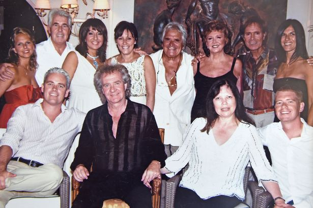 Sandro Morelli of Villa Tiberio with picture of Cilla with Cliff Richard and Max Clifford and other friends