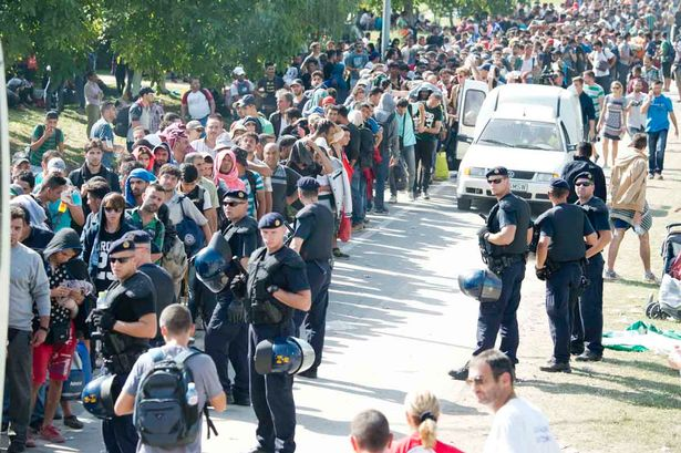 Refugees queueing for buses in a residential street near the railway station as tempers flair in the rising temperatures in Tovarnik, Croatia