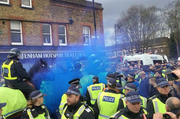 Horse mounted Police try and control fans with batons after blue smoke bombs are let off on the way to White Hart Lane