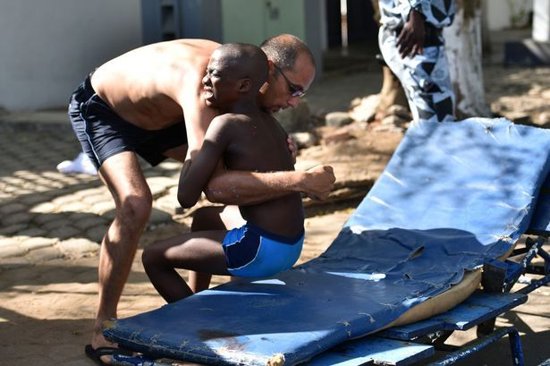A man helps a wounded child after heavily armed gunmen opened fire at a hotel in the Ivory Coast beach resort of Grand-Bassam