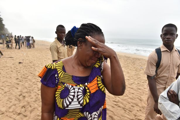 A woman cries at the beach as she looks for her son on March 14 , 2016 in Grand Bassam