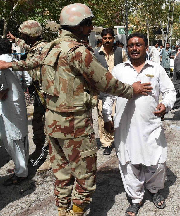 Pakistani soldiers comfort mourners after the death of victims in a bomb explosion at a government hospital premises in Quetta