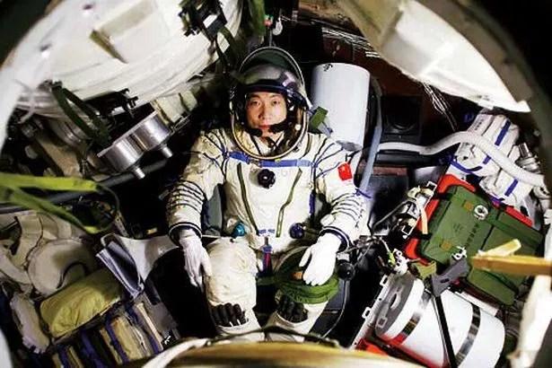 Chinese astronaut Yang Liwei sits in the module of Shenzhen 5 spaceship