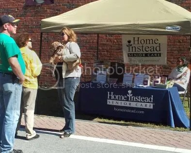 Deneen Evans speaking with visitors at Home Instead tent at fair.