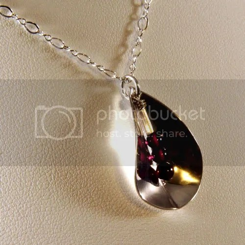 hand-forged sterling silver petal with garnet stamen