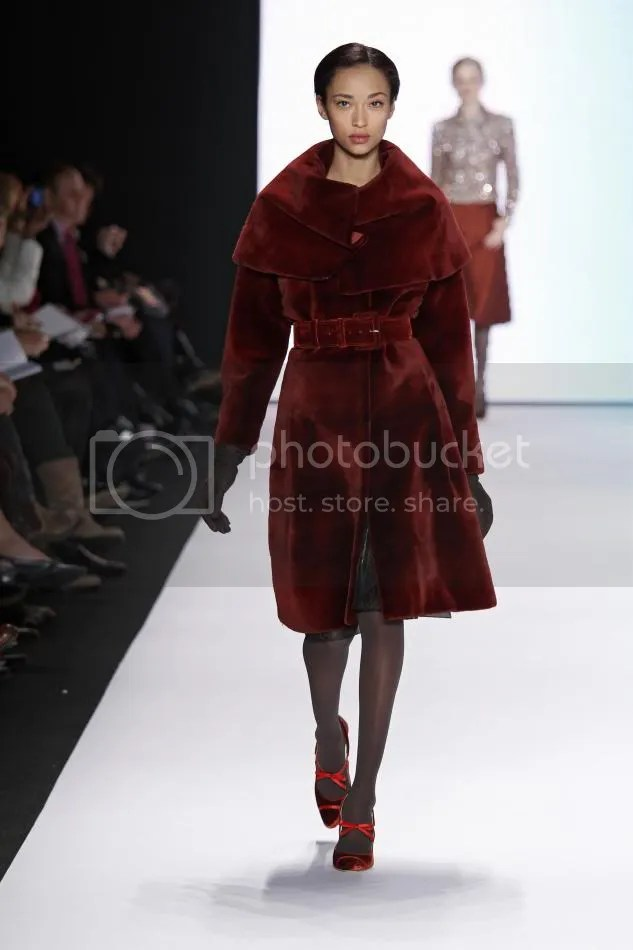 24. Anais: Rust sheared mink coat with caplet collar and rust velvet belt and black suede gloves.