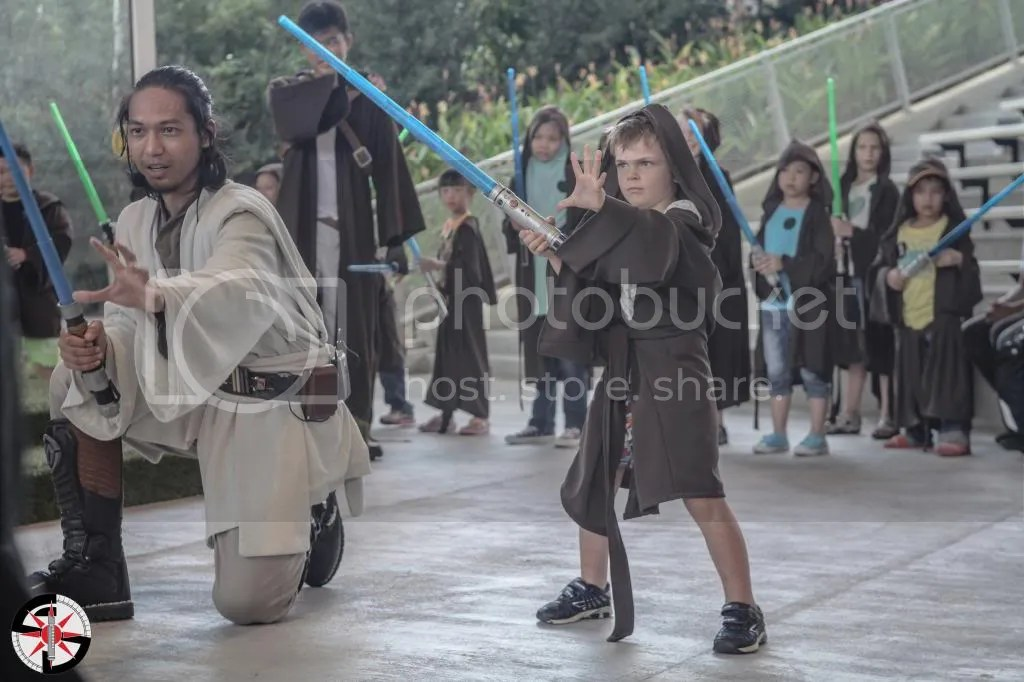 Master Sas-Ejiid guiding a youngling into battle with a Sith Lord