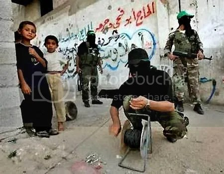 Hamas terrorists setting explosive charges while children watch