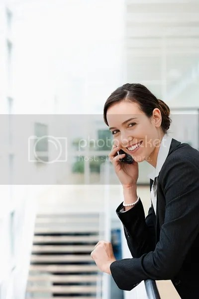 photo Young-businesswoman-talking-on-mobile-phone-and-leaning-on-railingsmiling.jpg