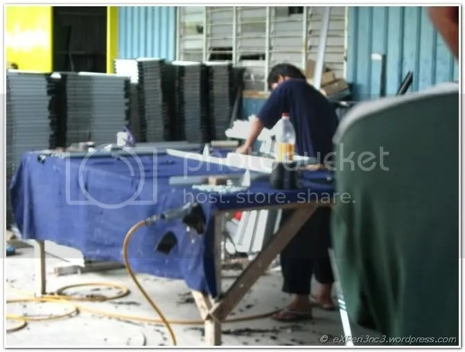 Workers assembling glass pane to frame