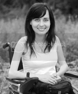 A black and white photo of a young woman with long hair sitting in a wheelchair in a field