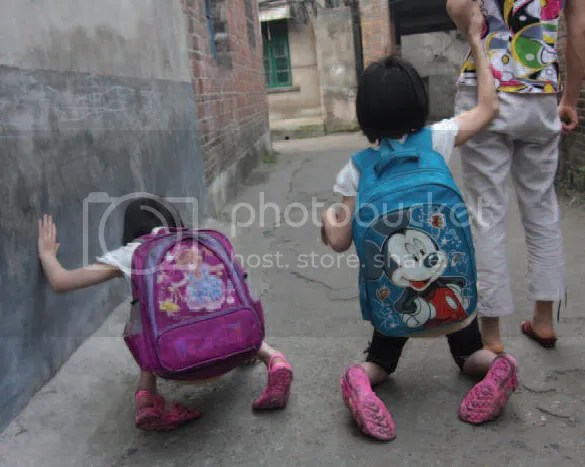 Two small children wearing backpacks walk on their knees beside an adult