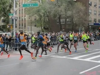 The elite men on First Avenue around Mile 17.5. Meb is in the white arm warmers behind the second guy in orange.