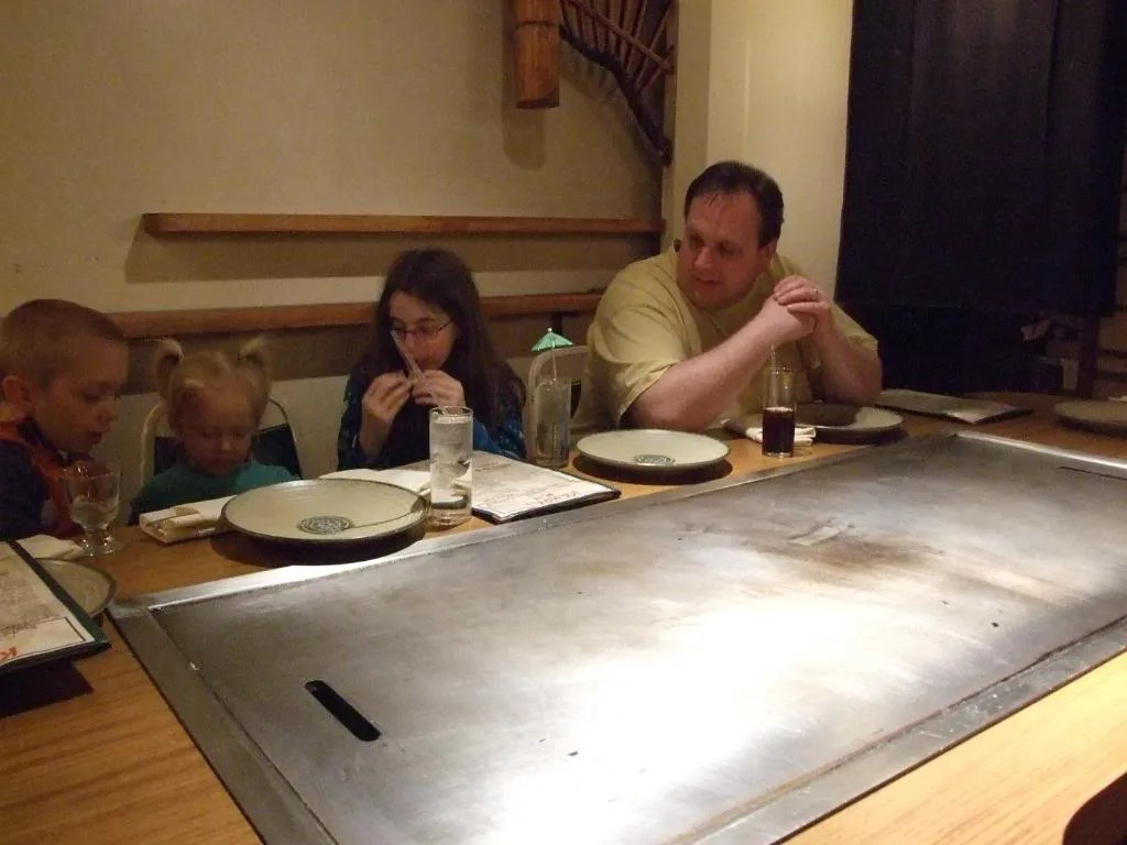 Emily shows Cecelia the finer points of paper umbrella's at a Japanese restaurant.