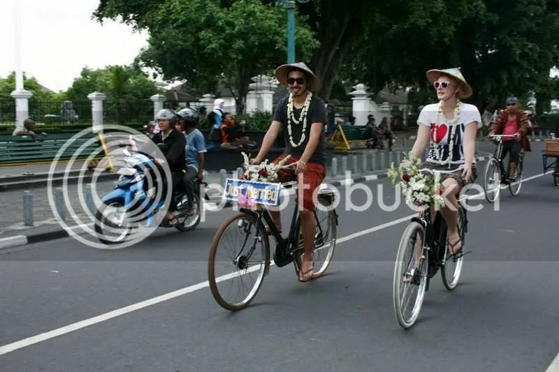 Pasangan Johan Sanjaya dan Kate Marais bersepeda melewati Gedung Agung dan diiringi oleh Jogja Onthel Club