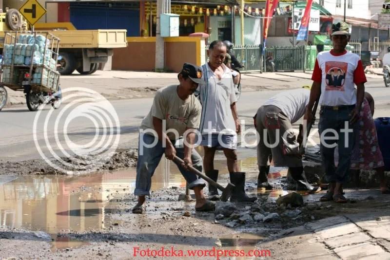 Masyarakat sekitar menambal lubang yang memakan korban saat jalan digenangi air ketika banjir. Ini merupakan insiatif dari warga gang Aman jalan Kemakmuran