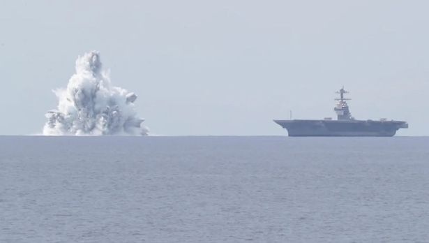 The USS Gerald R. Ford next to the bomb