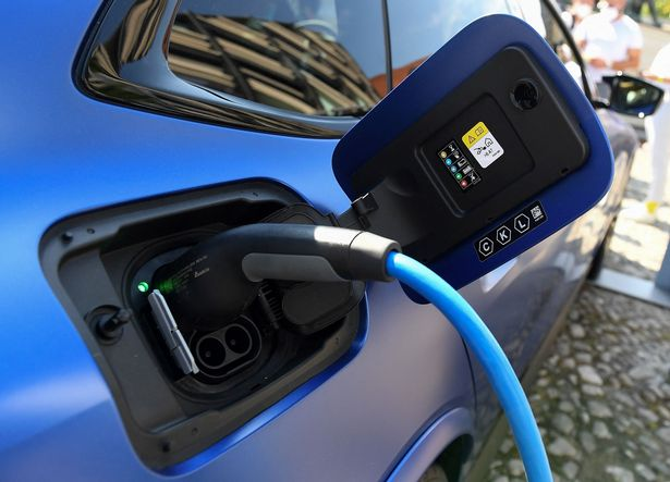 An electric car is charged at the stand