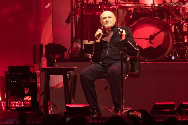 Phil Collins sits to perform with Genesis