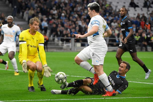 """French Former football player Samir Nasri (C) fights for the ball with German former goalkeeper Jens Lehmann (R) during the charity """"Heroes"""" football match between former Olympique de Marseille's players and Team Unicef, at the Velodrome stadium in Marseille, southern France, on October 13, 2021."""