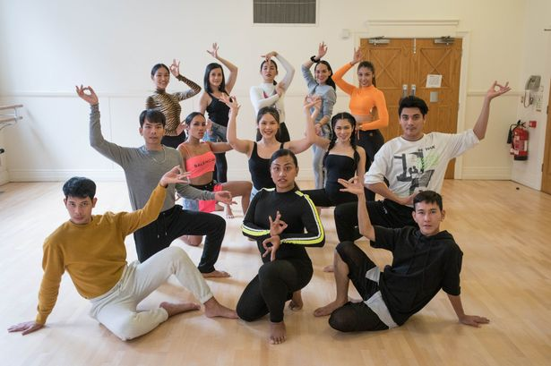 A group shot showing the cast of Ladyboys of Bangkok in a dance studio rehearsing