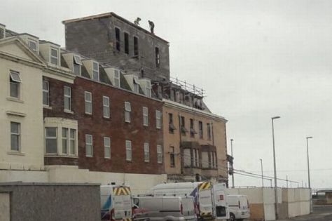 The workers were spotted five floors up on the roof edge
