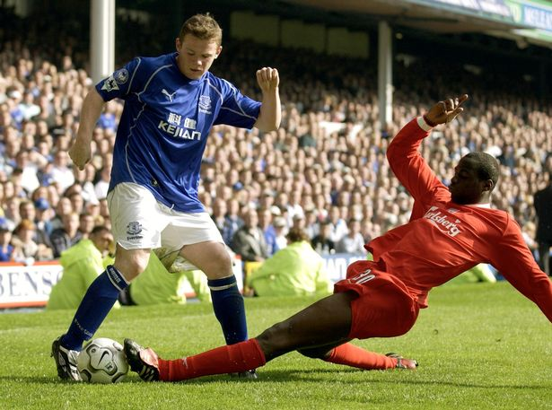 Wayne Rooney of Everton is attacked by Djimi Traore of Liverpool