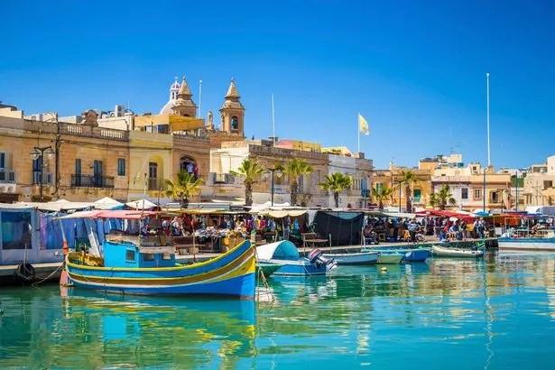 Marsaxlokk-Markt in Malta mit traditionellen Luzzu-Fischerbooten an einem schönen Sommertag mit blauem Himmel und grünem Meer