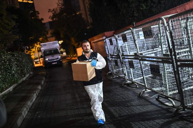 A Turkish forensic police officer is seen carrying a box at the consulate in October