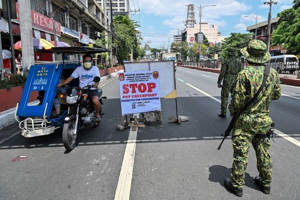 Philippine police man a checkpoint on the border between Quezon city and Manila districts (photo not directly related to story)