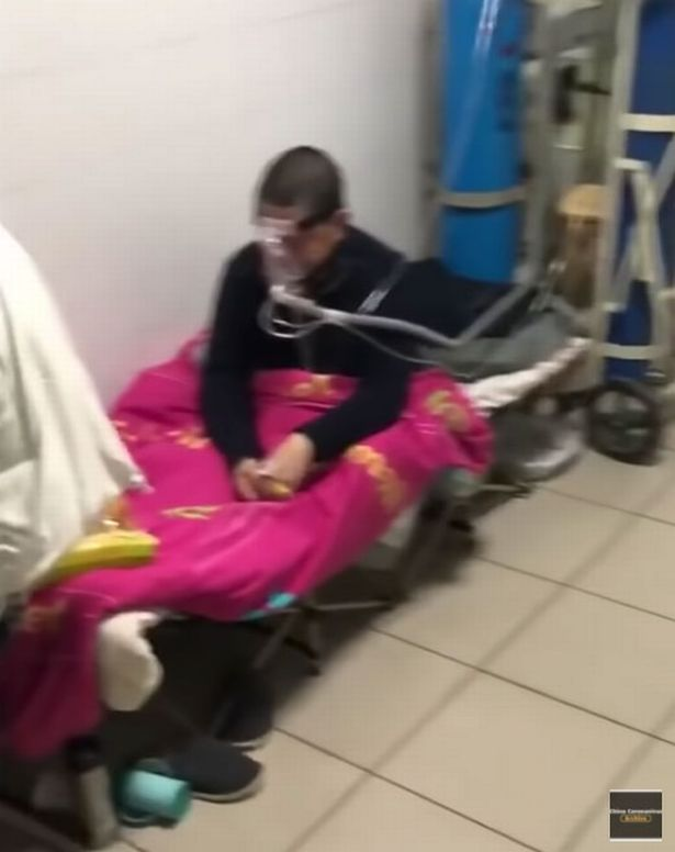 A patient receives oxygen as he sits on a hospital bed in a corridor in Wuhan