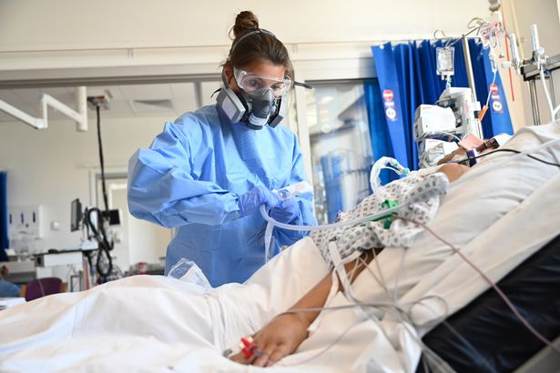A clinical medic in PPE cares for a patient in ITU at Royal Papworth Hospital in Cambridge